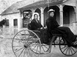 Roberta Hopp and Lucy Hopp in carriage in front of Pingenot home and postoffice, Castroville, Texas