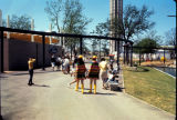 HemisFair'68 tour guides and visitors walking near the base of the Tower of the Americas.