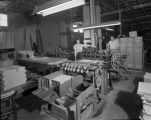 Employees beside printing equipment in Maverick-Clarke Litho Company, 215 E. Travis Street